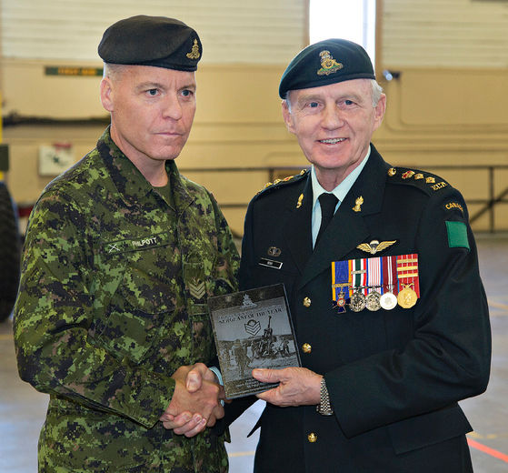 Sgt. Grant Philpott (left) of the 56th Field Regiment Royal Canadian Artillery is presented with the